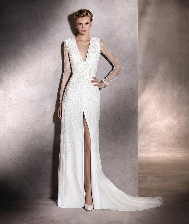 La robe de mariée ANTARA est un modèle urbain réalisé en tulle moelleux  orné de pierres fines, à manches longues, coupe évasée et décolleté en V  provocant