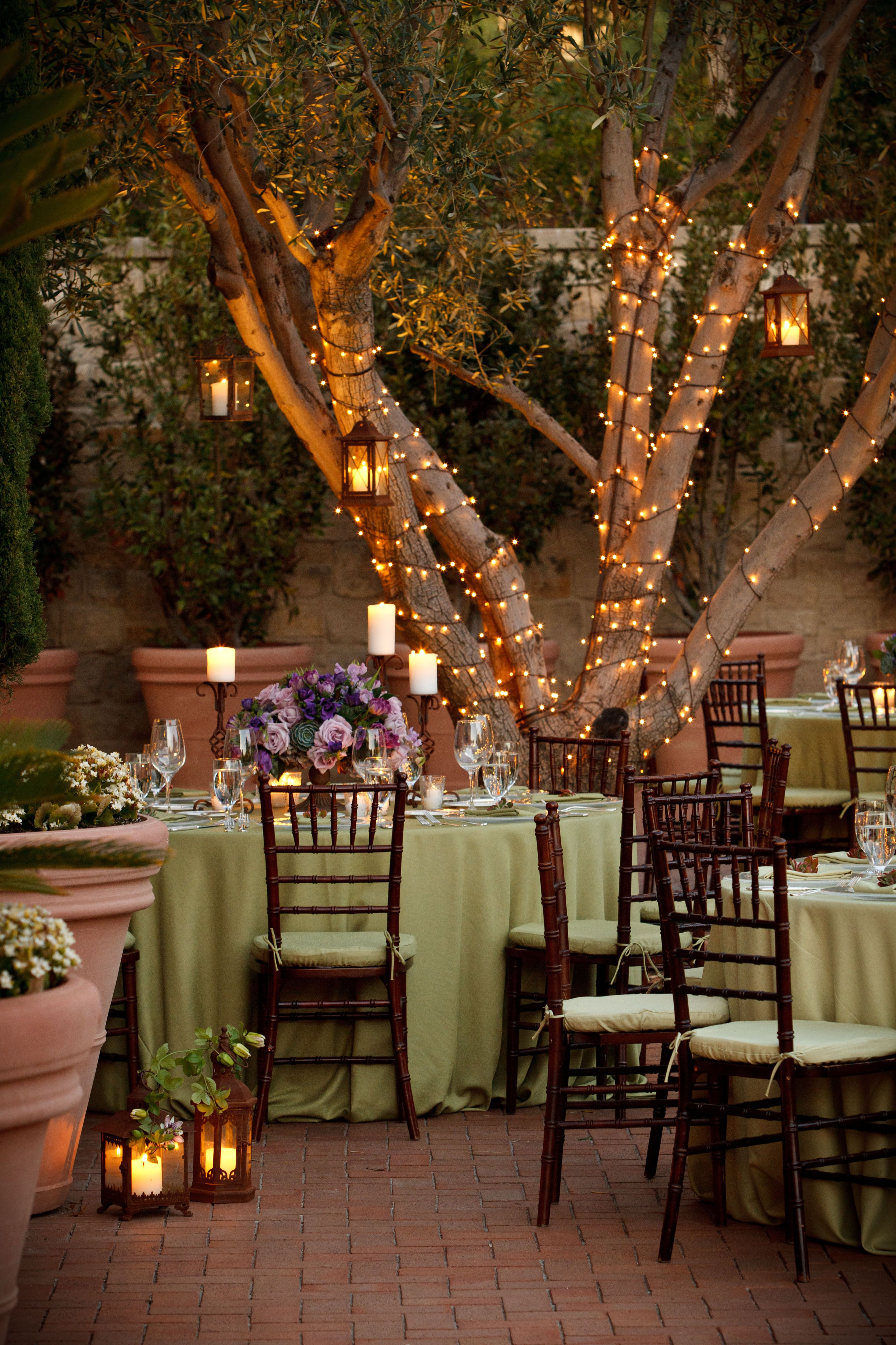 Evening alfresco dining outdoor lighting hanging lanterns olive green linens purple roses venue the resort at pelican hill