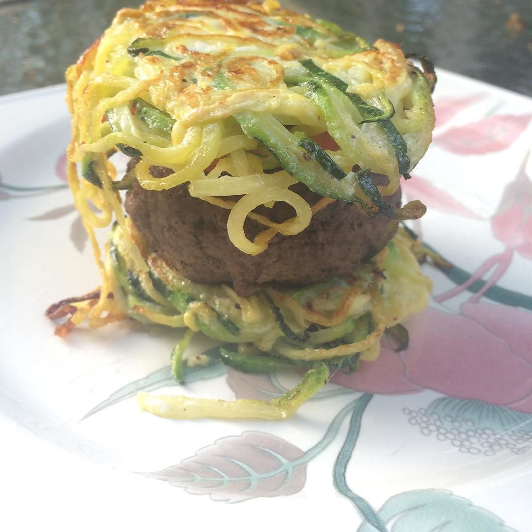 Hamburgers in a zucchini bun - the most delicious pairing I've discovered so far! To make the zucchini bun: -spiralize 3 zucchini's -mix the spiralized zucchini in a bowl with 3 egg whites -flatten the zucchini/egg mixture in a remekin or a bowl that is the bun size you desire; place a piece of parchment paper over the zucchini and flatten it down with a can -refrigerate for approx 30 min or more to hold it's shape -cook on a frying pan on both sides #paleo #zucchini #hamburger…