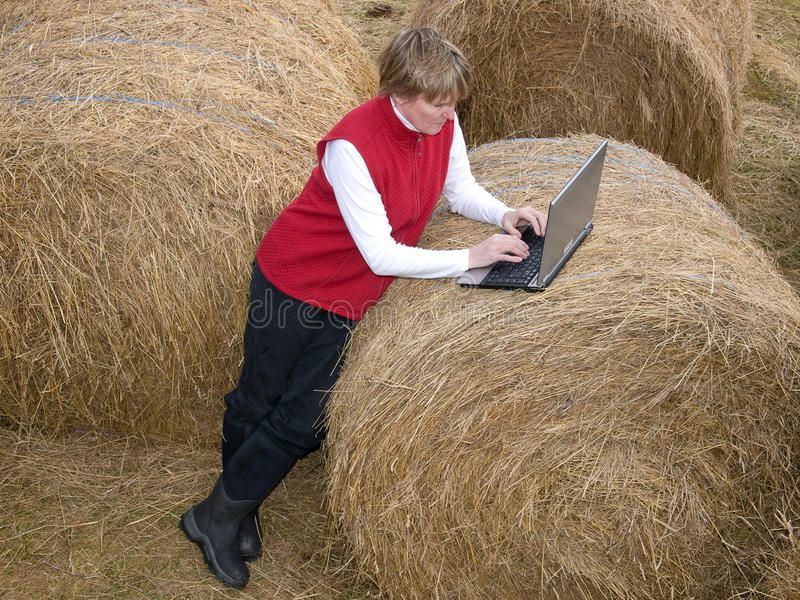 Woman working wireless in the country. Woman working on laptop with wireless con ,