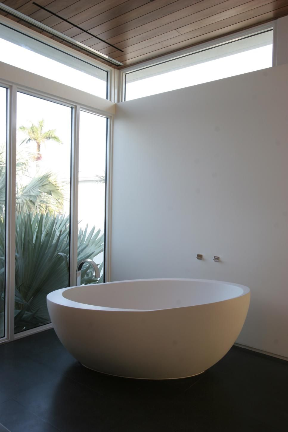 A small freestanding tub sits in a corner with floor-to-ceiling ...