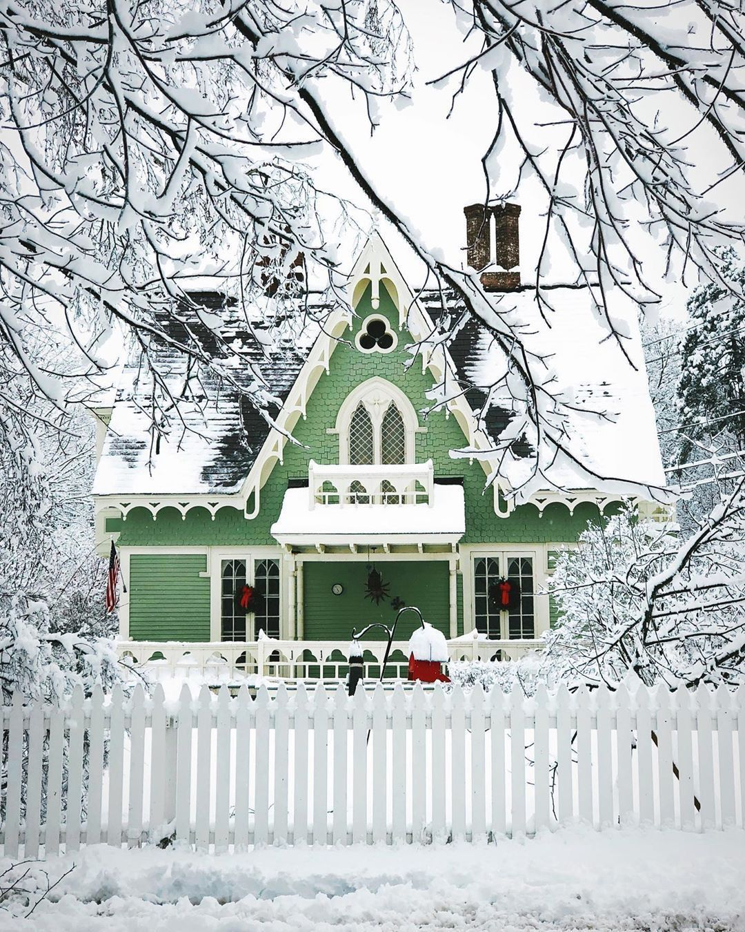 Mint green cottage with white gingerbread trim and picket fence
