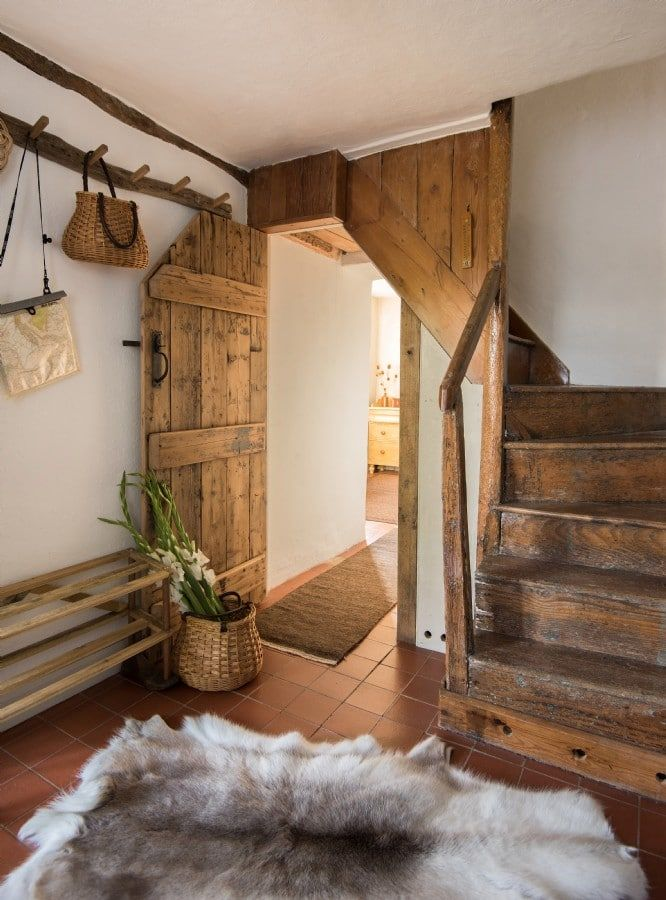 love this rustic country farmhouse staircase hallway with rustic wooden stairs, tiled floor and hide rugs. Click through for more modern rustic farmhouse interiors ideas you'll love