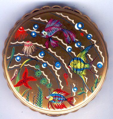 So pretty, this frilly bottomed compact has wonderful colours. The compact is done in matt gold tone metal with a great picture of tropical fish painted on the top