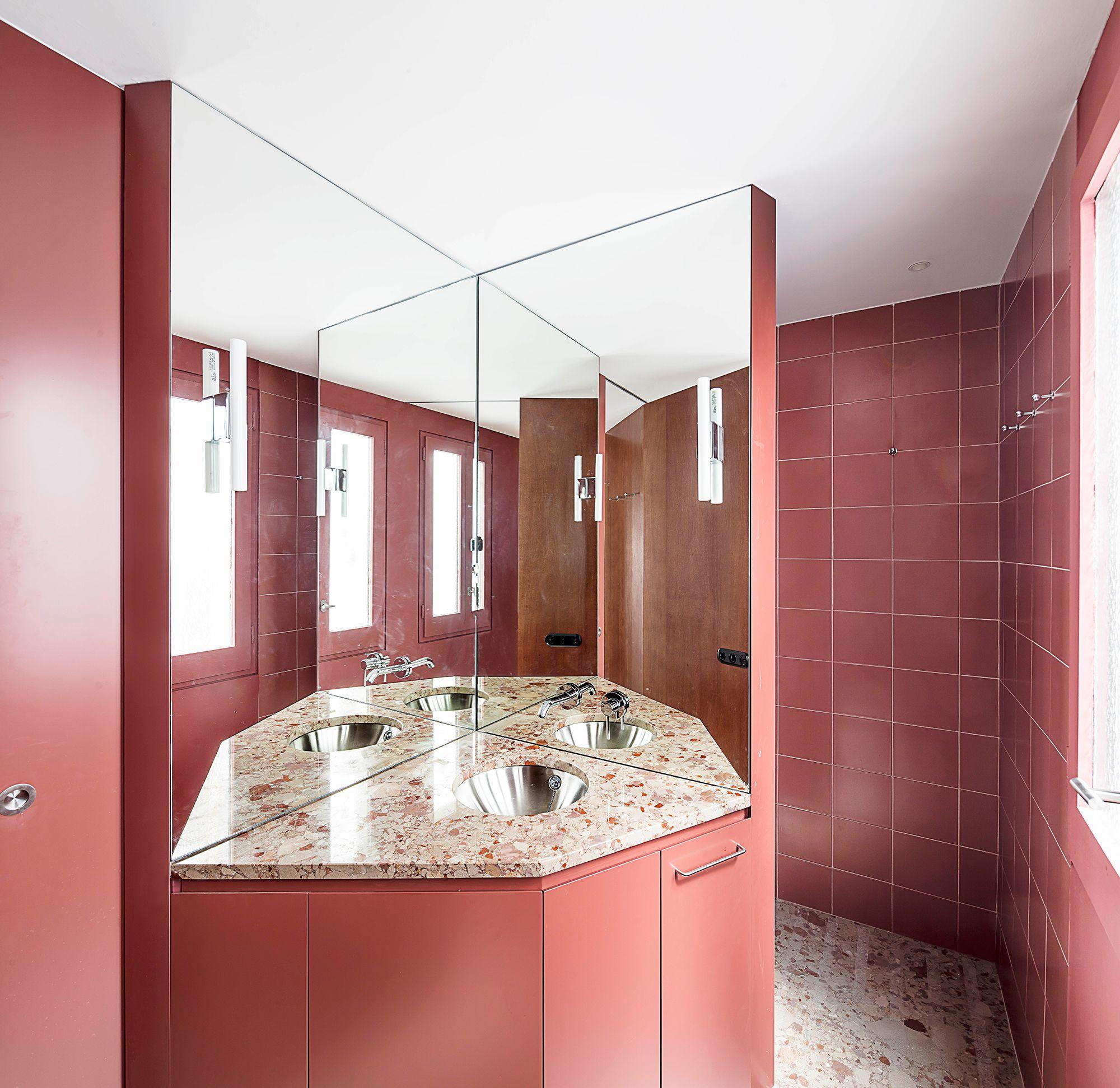 Baño granate con mármol rosa en la reforma de un piso en ...