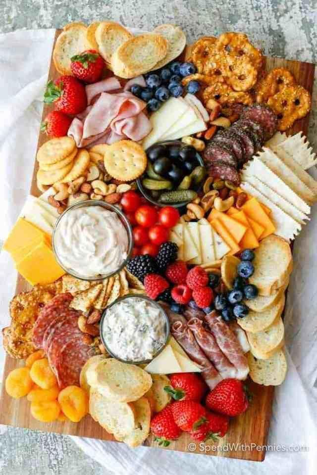 DIY Charcuterie Board. 41 Easy New Year's Eve Appetizers | Looking for easy party appetizers, finger foods, and canapes for a crowd? These make ahead party appetizers are perfect for New Year's Eve party, for birthdays and other holiday parties. You can find party appetizers: garlic cheese bread, dips, cold appetizers and cheap snacks if you're on a budget. #partyappetizers #fingerfood #canapes #newyearseve #appetizers #makeaheadappetizers