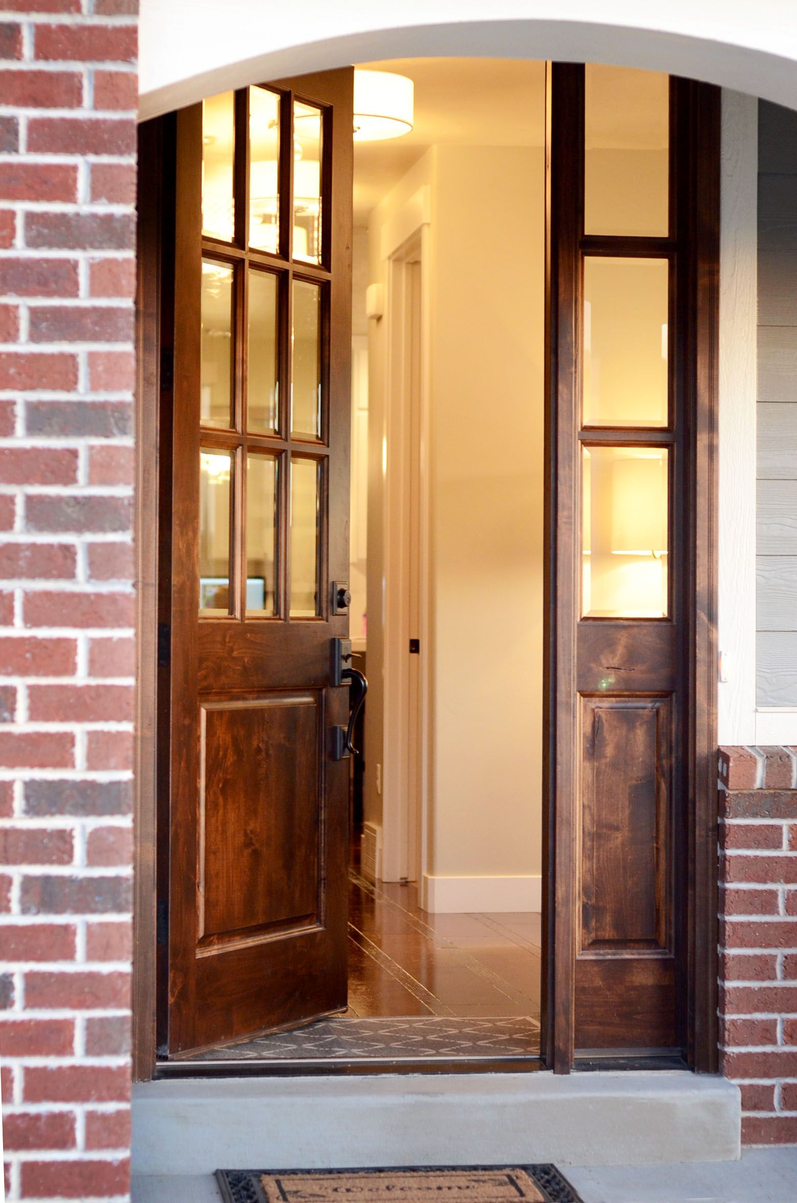 Wooden French Doors Add Class To This Brick Home S Entryway Wood Front Doors French Doors Exterior Garage Door Colors