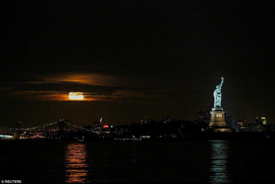 De supermoon wordt gezien door wolken boven New York, gezien vanaf Bayonne in New Jersey