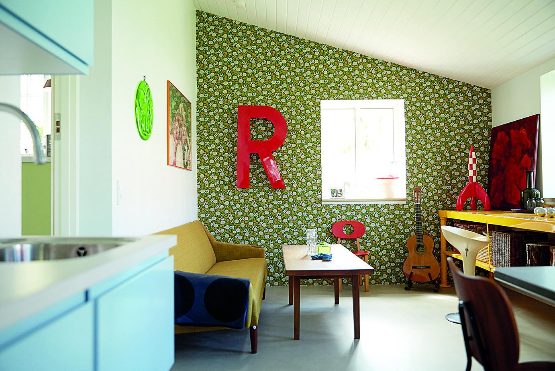 En storblomstret grøn væg med et stort R sætter retro-stilen i familien Mengers retro-køkken.