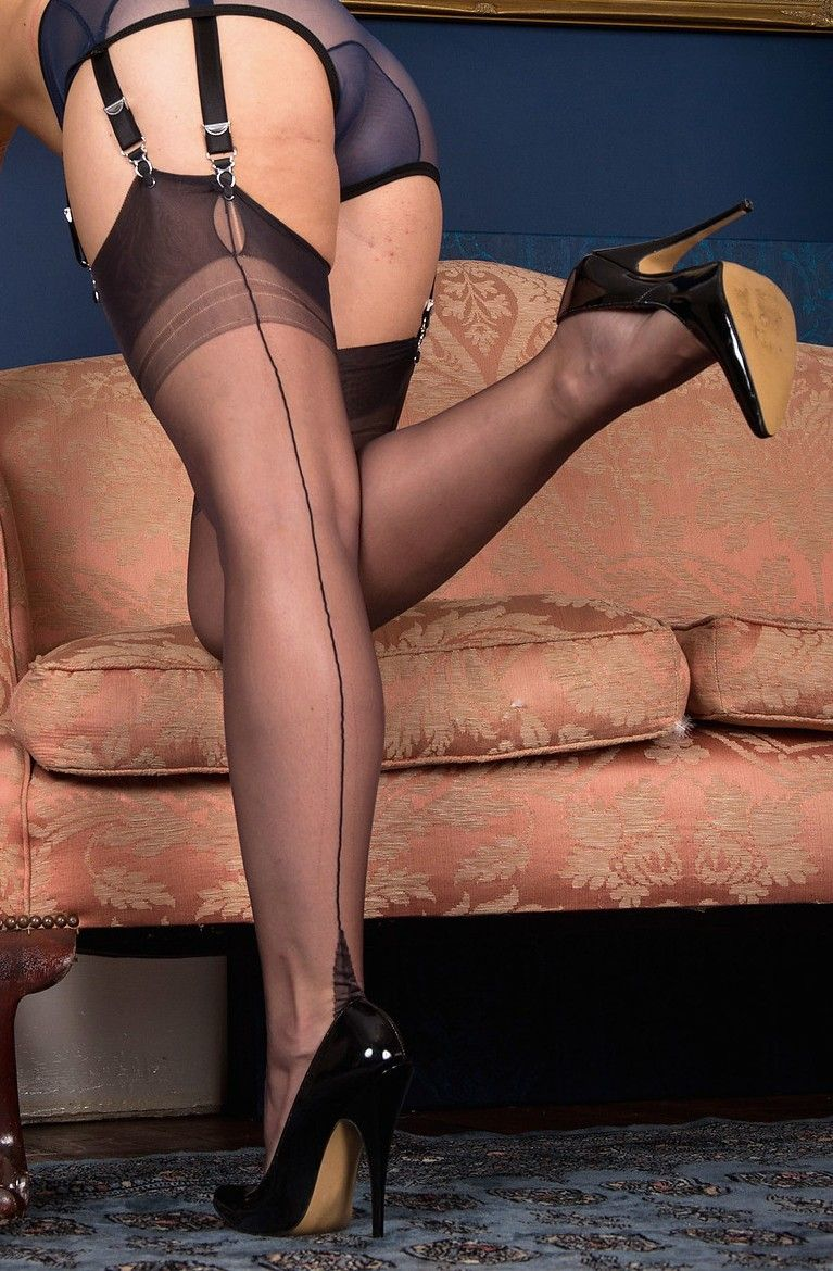 1fcb5745c Black suspenders with black Fully Fashioned stockings and glossy black heels  by a woman on a sofa.
