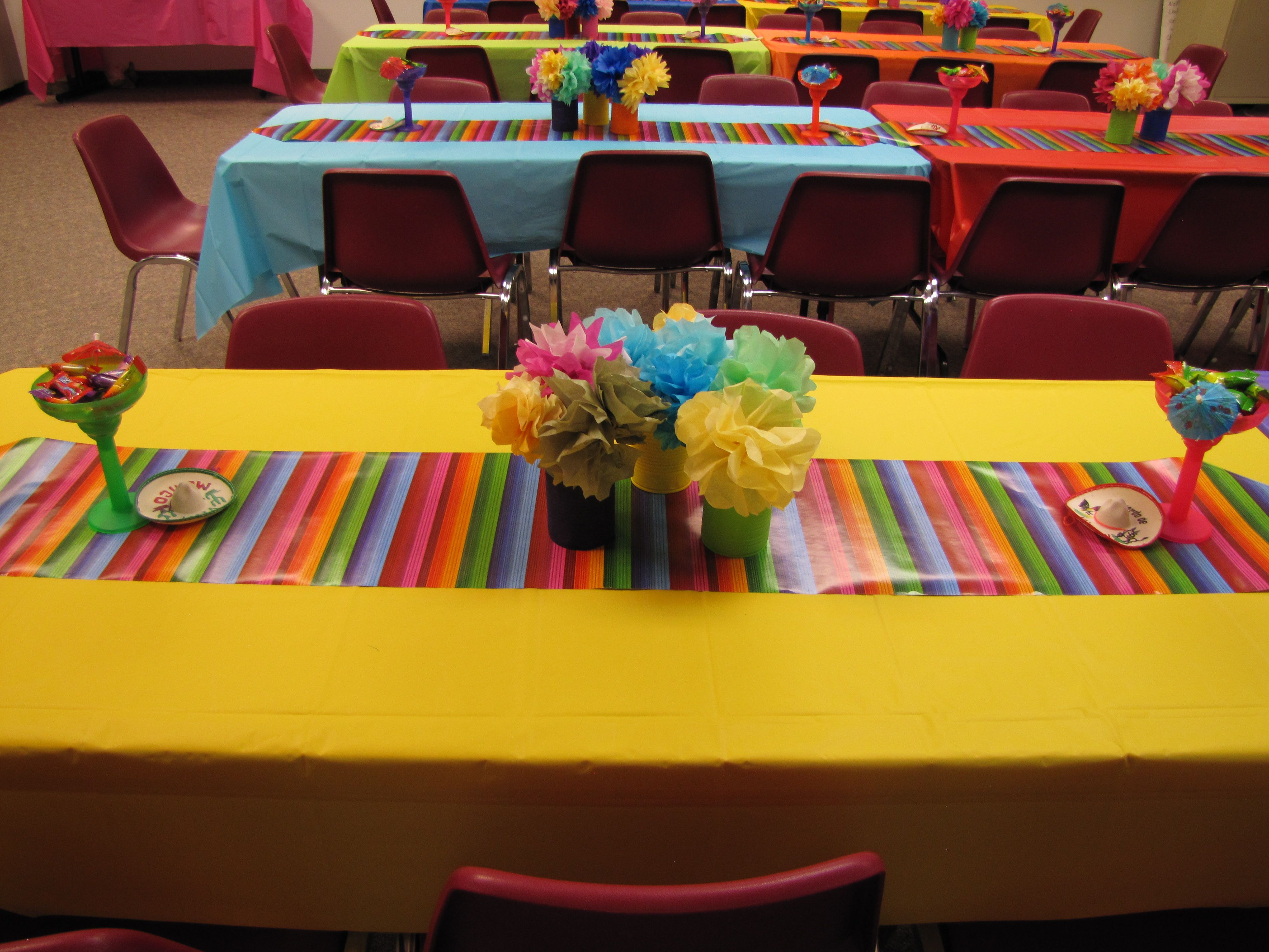 Various Brightly Colored Tableclothes A Serape Table Runner The Centerpiece Is Made Up Of Paper Flowers In Painted Cans Mini Sombreroargarita