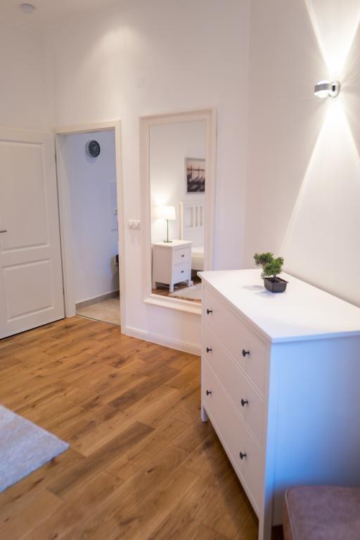 Weiße Kommode und Ganzkörperspiegel als Schlafzimmer-Einrichtung