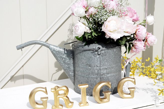 Wedding reception: galvanized watering can full of fresh posies, gold letters spelling out last name.