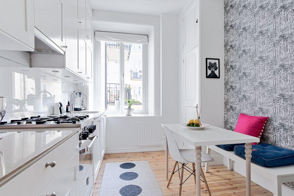 Köksskåp från Ballingslöv med vita luckor och modern glasskiva som bänkskiva och stänkskydd