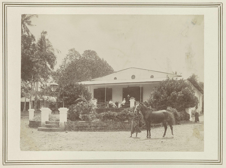 Kassian Céphas   Woonhuis, Kassian Céphas, 1886   Twee mannen zittend op de veranda van een woonhuis. Op de voorgrond een Indische bediende met een paard. Onderdeel van het fotoalbum aangeboden aan J.M. Pijnacker Hordijk bij zijn vertrek uit Jogyakarta in 1886.