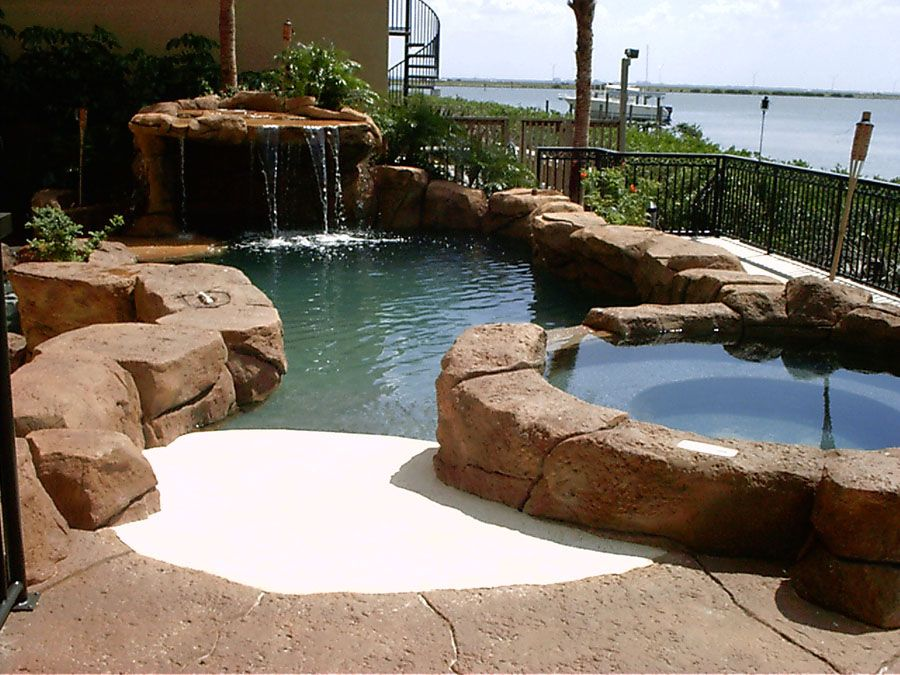 Pool spa beach entry grotto water fall weeping wall for Pool surround ideas