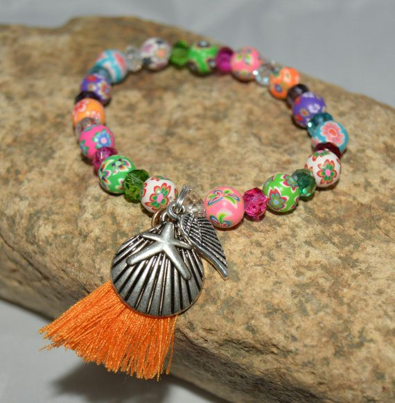 This fun, multi colored, beaded stretch bracelet is perfect for the summer, those who love the beach and has a pretty, small tassel along with a clamshell/starfish charm and an angel wing. Just looking at this bracelet makes you think of summer, the tropics, the beach, a relaxing vacation and wonderful memories. I used polymer clay beads and small Swarovski crystal beads in various colors to bring out the colors in the clay beads.