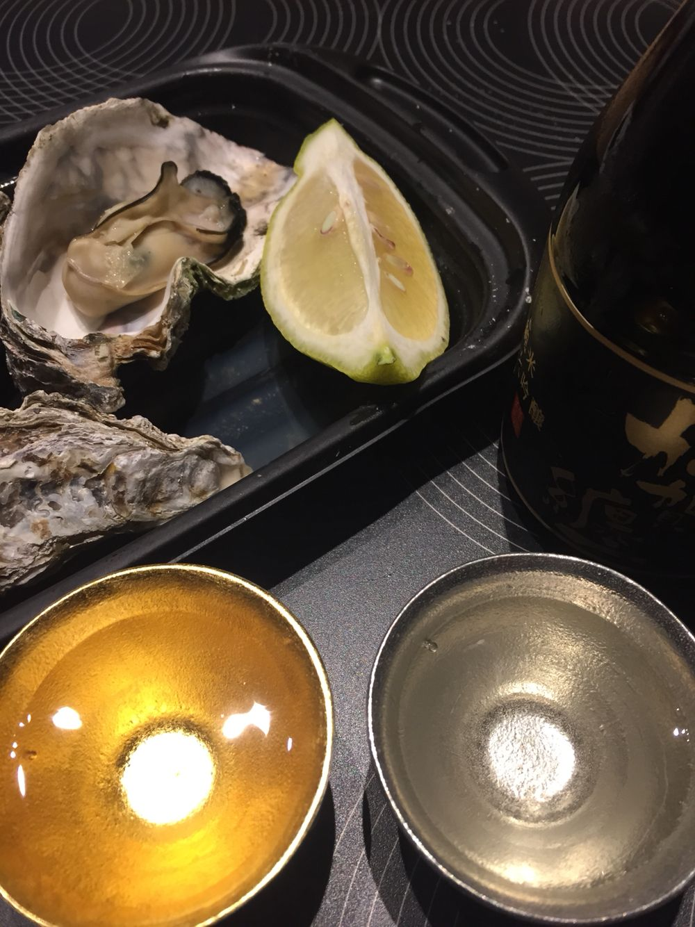 Small Japanese sake cups of tin(the left one coated with gold leaf) served with steamed oysters