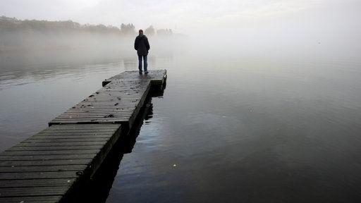 Ein Mann steht einsam am Ende eines Bootsstegs und schaut auf den Nebel am See. | Bildquelle: WDR/dpa/Mikko Stig