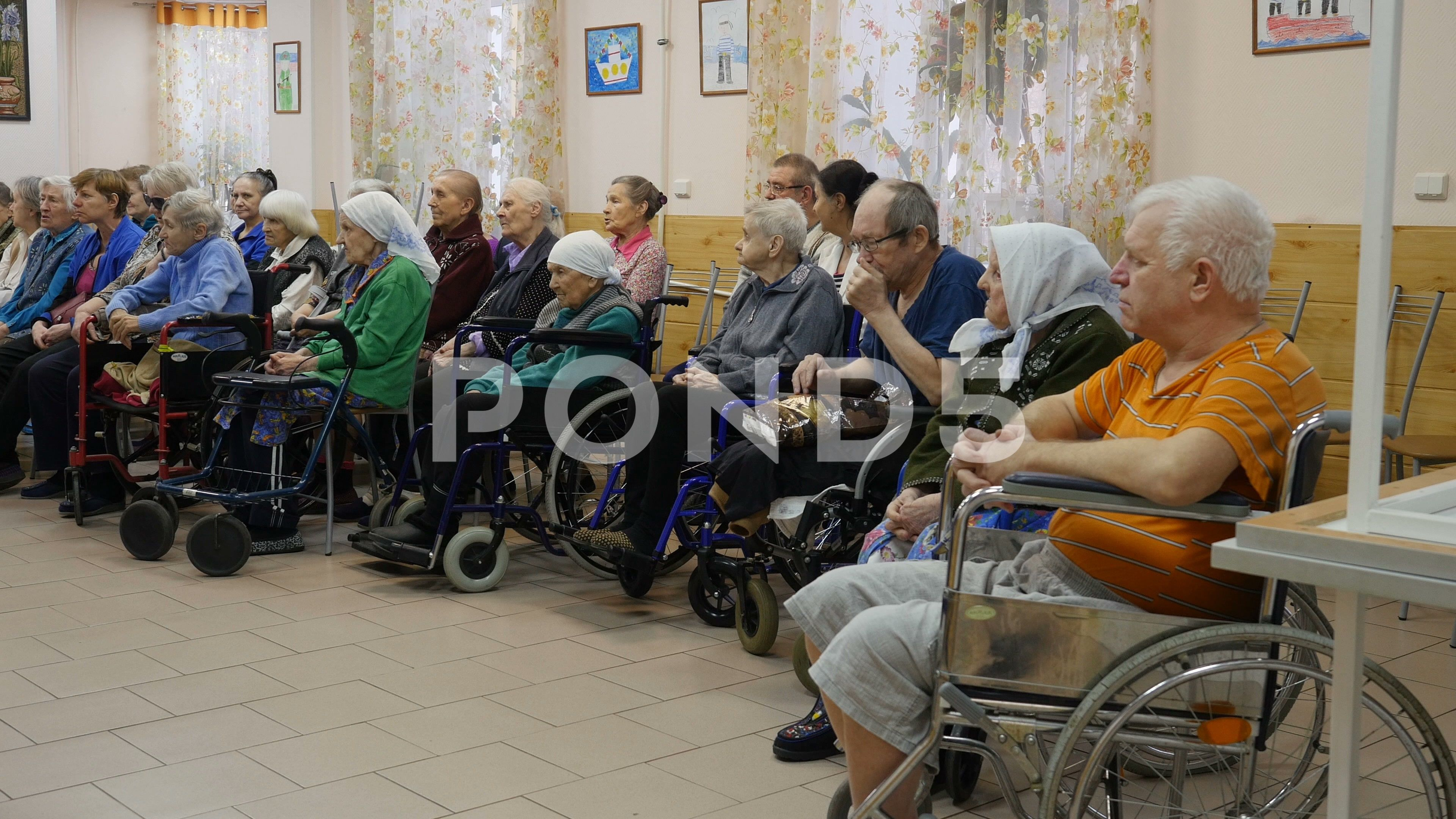 Elderly people with disabilities sitting at nursing home
