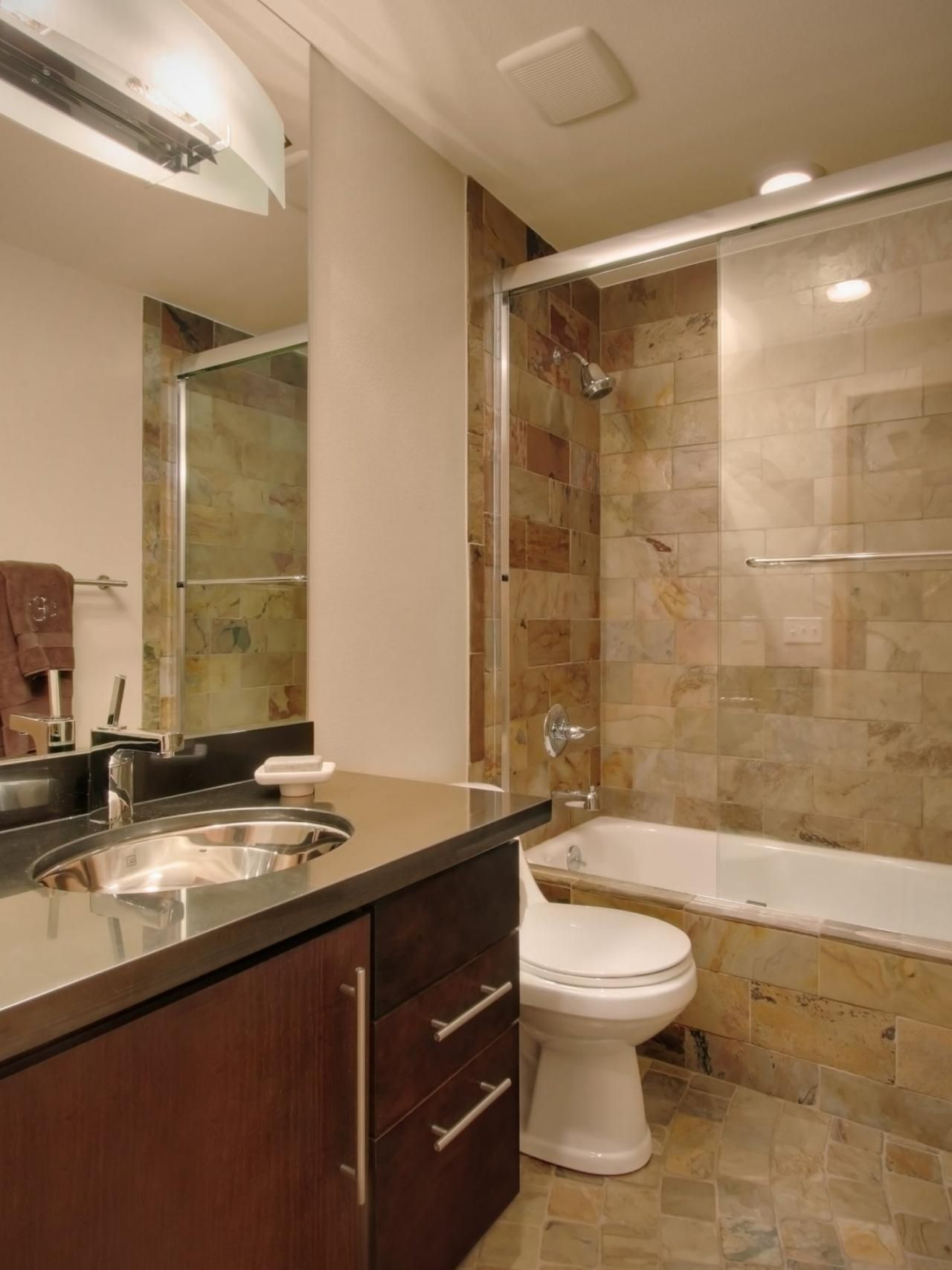 An earth-toned tile shower is the focal point of this ...