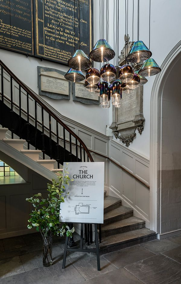 A cluster of Tom Dixon's Flask Oil Pendant illuminates the staircase of the 18th century church at Clerkenwell Design Week