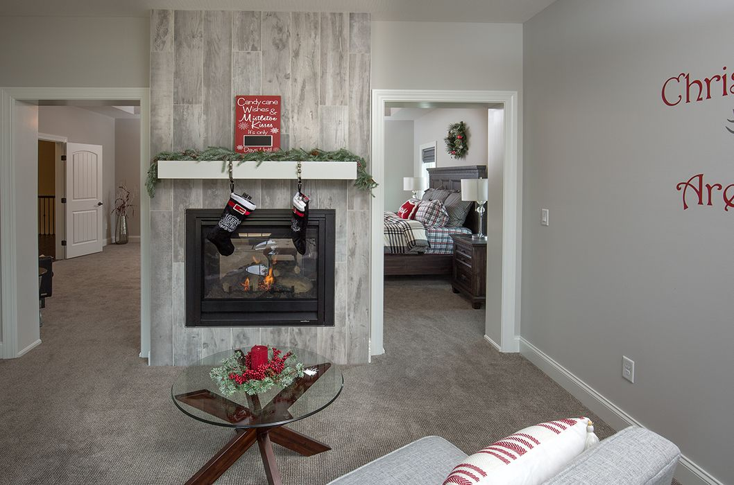 The wood look tile on this fireplace gives this master bedroom a ...