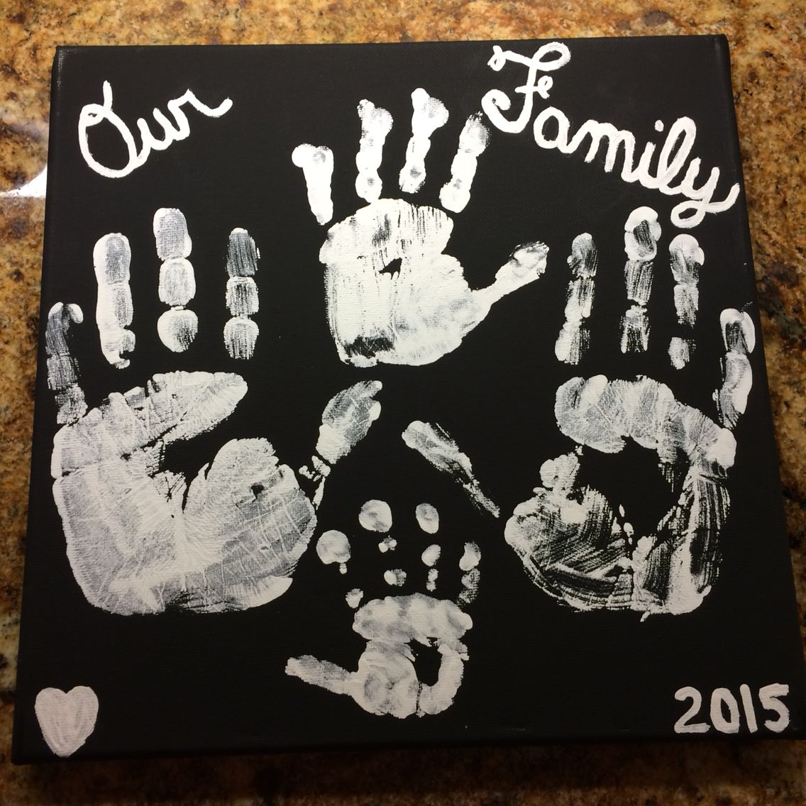 Family handprints white acrylic paint on black canvas for the