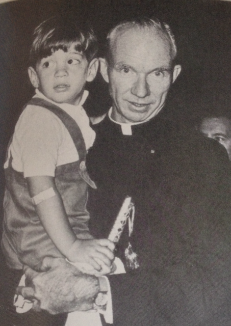 """kennedycamelot: """" 1964: Reverend Richard McSorley with John Jr. at the World's Fair in New York City. """""""