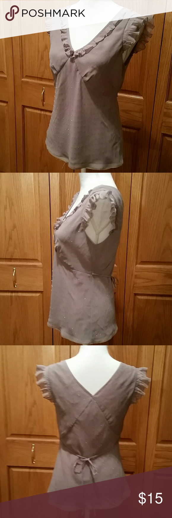 NWOT Ann Taylor LOFT Taupe Camisol Type Blouse Very pretty and feminine this blouse is two layers, one being a liner. Ruffled neckline and tie backs on the side. No zipper just a more open cut that slips overhead easily. 100% polyester with soft flecks of silver threading throughout that make this pretty top sparkle. Breastline across laying flat measures 17. Shoulder to bottom of top measures 23 inches. Never worn. LOFT Tops Blouses