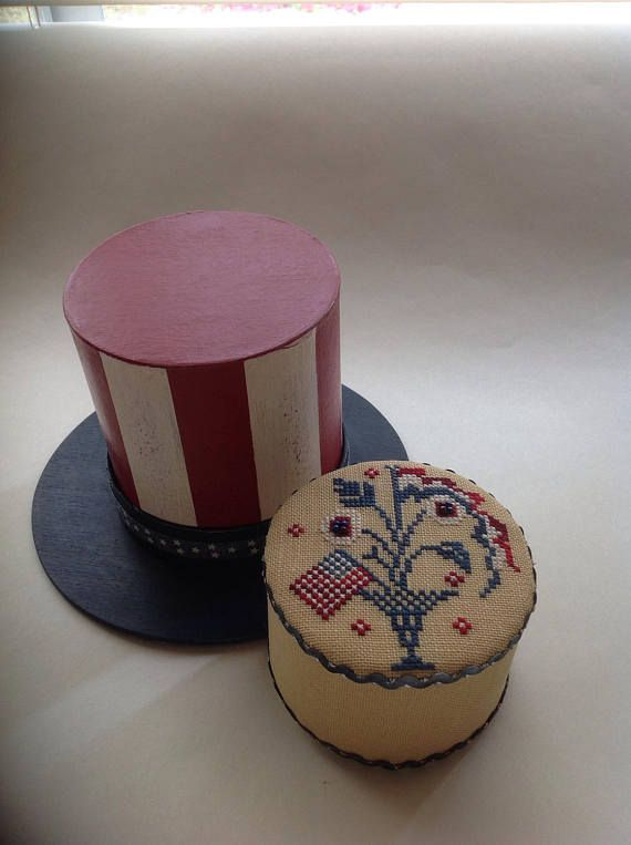 This is a Americana piece that is painted to look like uncle sams hat. It holds a cross stitched Americana pin drum. This piece is stitched on a tea color French linen with over dyed cotton threads. The pin drum measures approx. 3 inches across and 2 inches high. It is filled with a coiled cotton batting so you can stick your pins into the side if you wish. I have trimmed this piece in a beautiful hand dyed German ric-rac with silver threads running through it...its just lovely! The hat is…