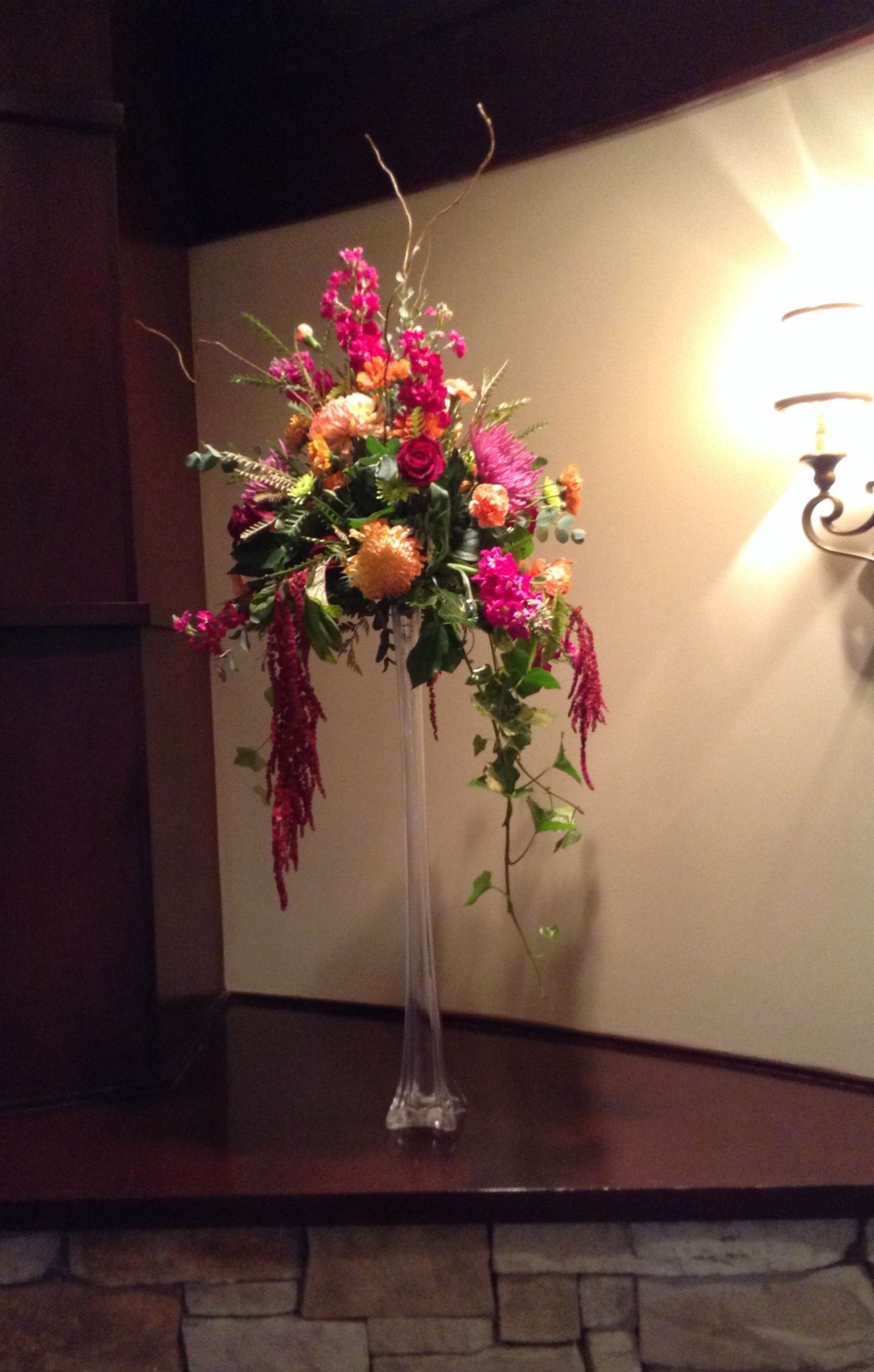 Reception flowers in tall tower vase by