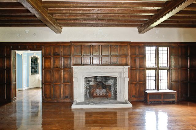 Room with wood paneling ceiling beams tudor arch for Tudor style fireplace