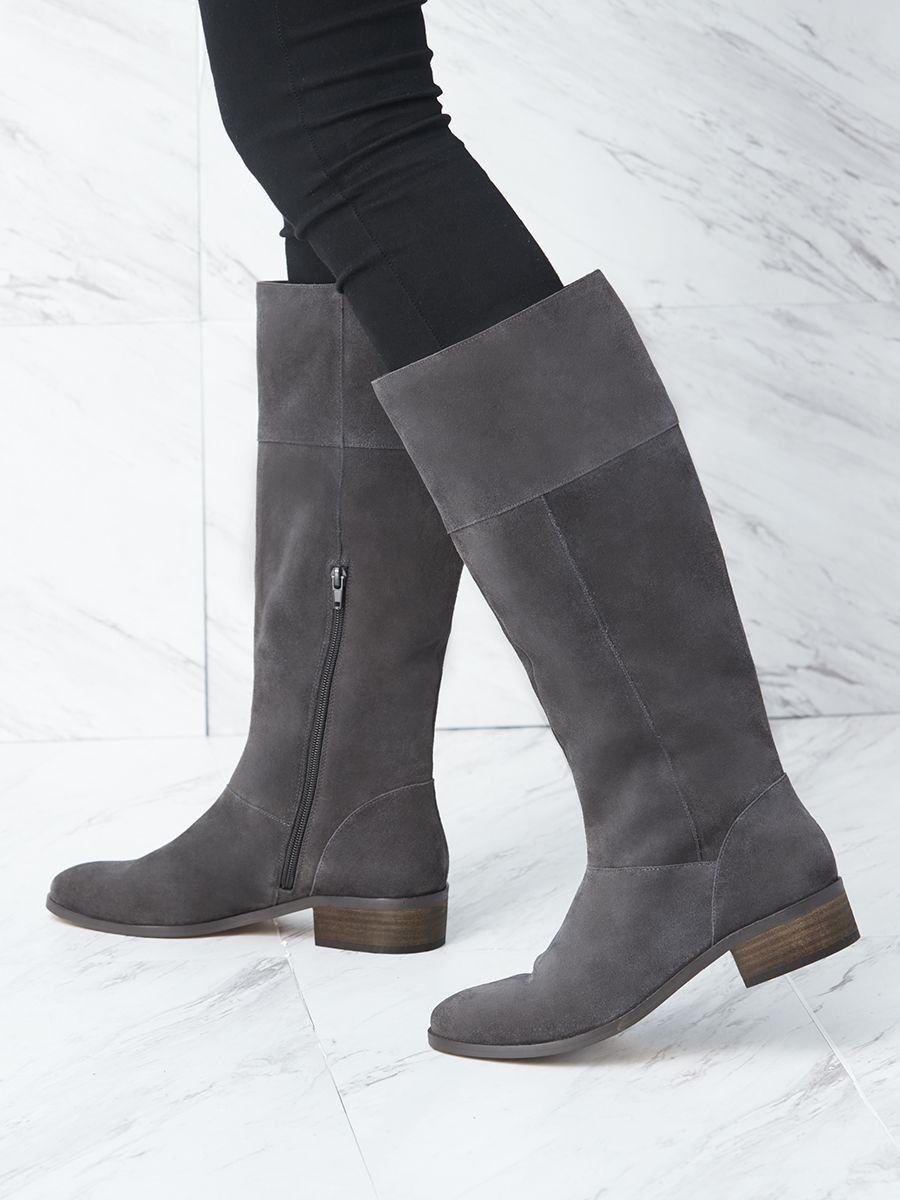 59775b84f10 The classic flat boot with a low stacked heel and knee-high construction.  The Carlie boot also features an inner zipper for easy on and off wear.