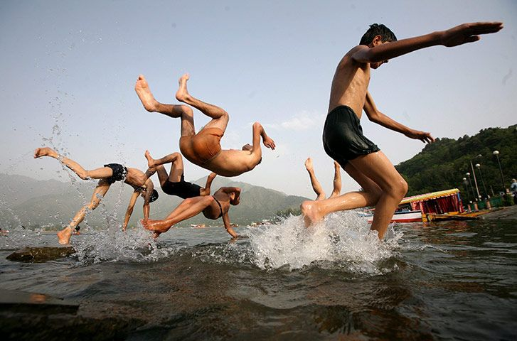 Srinagar, Kashmir: A group of boys jump in Dal Lake