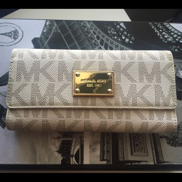 Michael Kors Wallet Pre-loved but still in great condition aside from the cracks in the edge of the folding. Its a tri-fold, has 4 slide pockets 7 credit card slots 1 id slot also zip coin pocket in back..Will trade only for MK silver stainless steel watch of my liking..Feel free to ask questions😃... PRIVATE offers welcomed😃 MICHAEL Michael Kors Bags Wallets