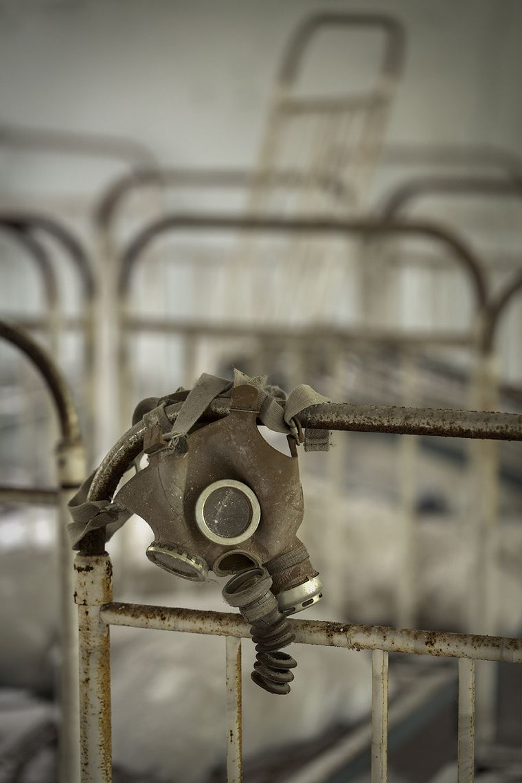 Child's gas mask hanging off the end of the bed, Pripyat.