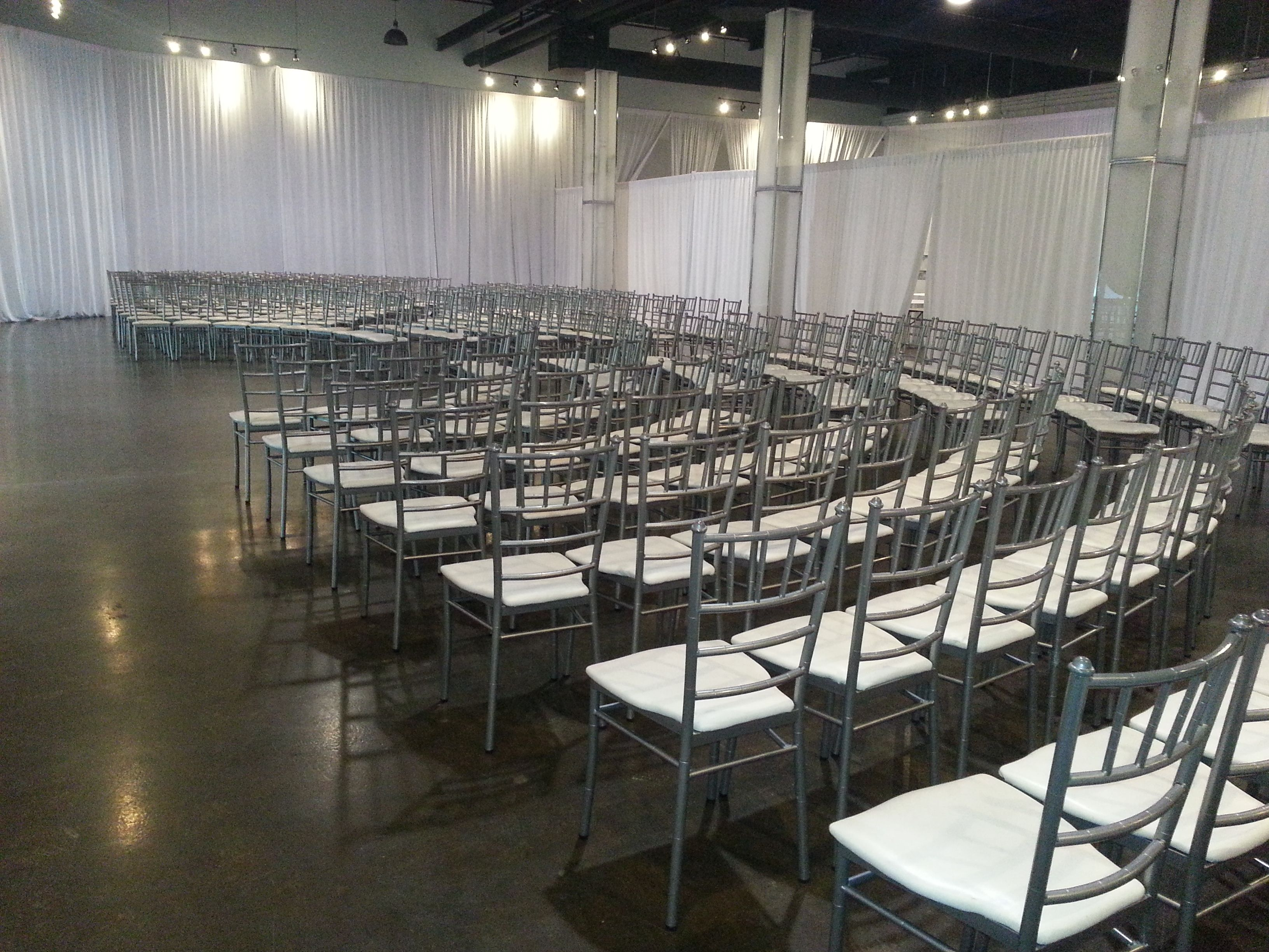 Setting Up For A Wedding Ceremony At The Warehouse Event Venue White Draping Sliver