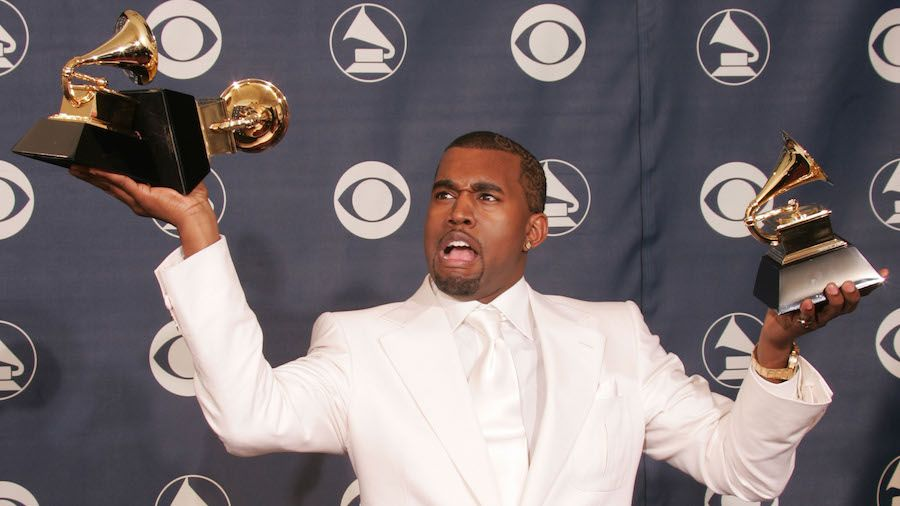 23 In Celebrity Fashion Kanye Holds Up His Well Deserved Trophies It Would Appear That His Astounding Success And Acclaim Are Paving Kanye West Kanye Grammy