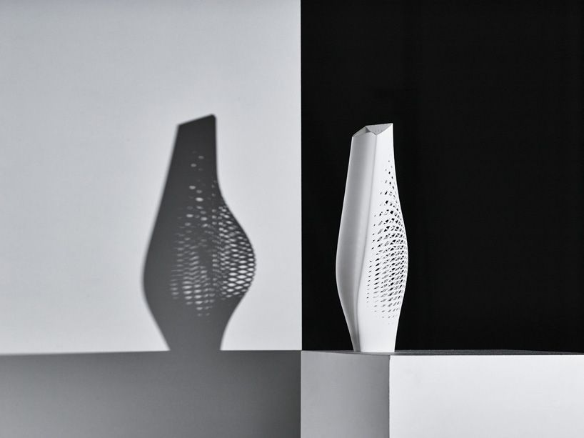 The curves of the vase are exaggerated in its shadow.