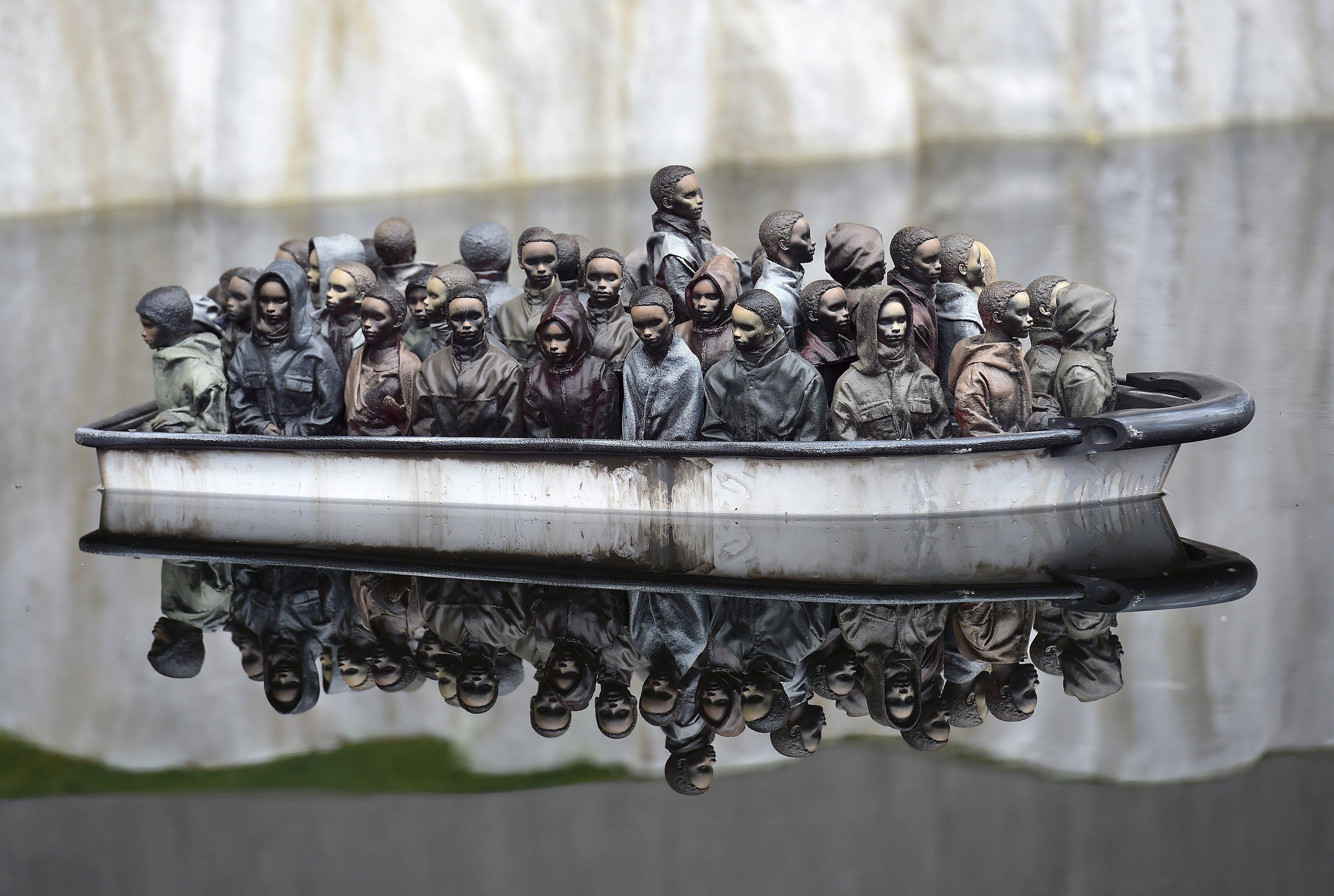 Na #Europa, artistas de rua têm chamado atenção ao retratar em suas obras a crise de refugiados do continente. É o caso de #Banksy, que em sua recém-inaugurada #Dismaland confeccionou uma instalação que reproduz barcos de refugiados em um lago. Foto: Toby Melville/Reuters.