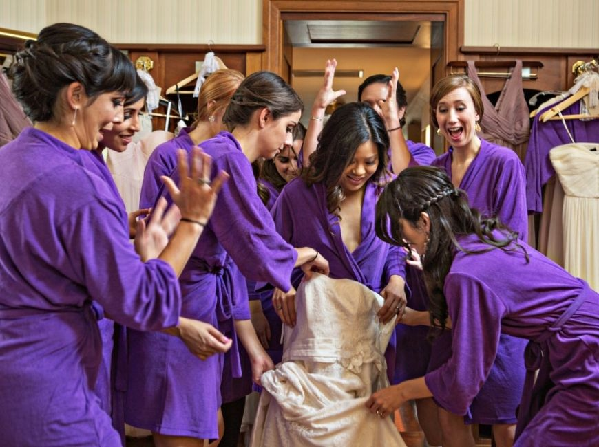 Stylish bridesmaids getting ready in purple terry cloth robes with ...