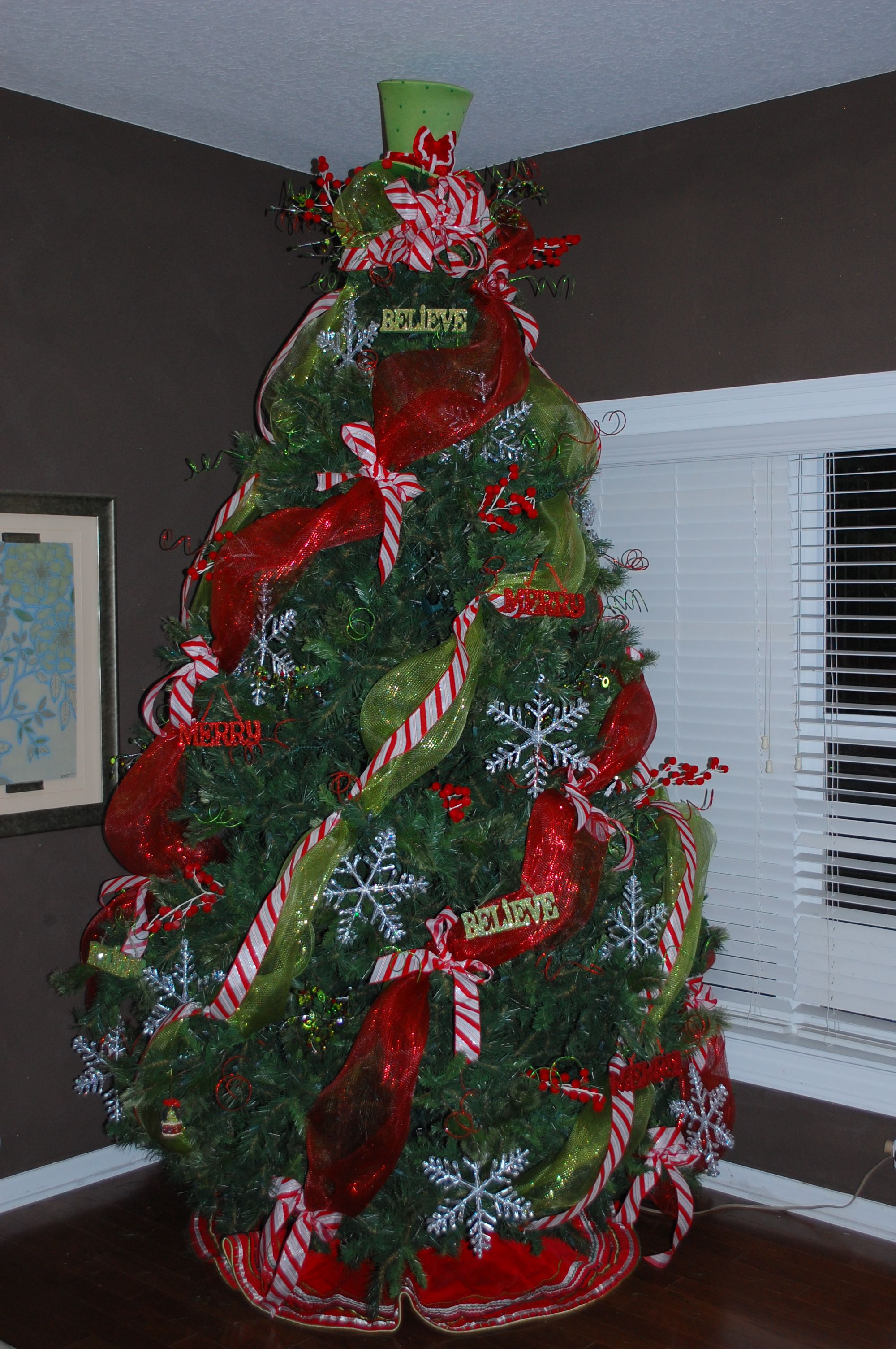 Getting started on the tree with mesh, ribbon, topper, sprigs, and large  ornaments
