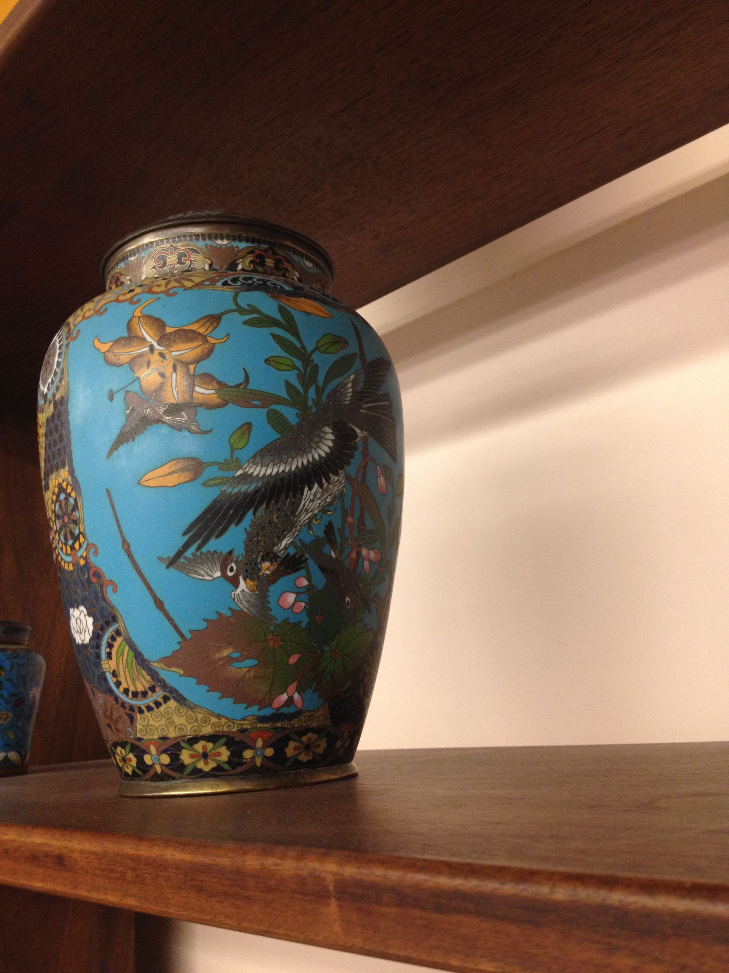 This is an oriental vase found in the rare collections room in the library. it is blue and depicts birds surrounded by flowers. there is very obvious oriental influence.