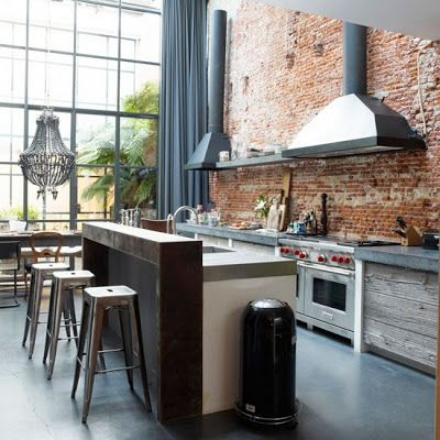 open concept kitchen w/ overheight ceilings & exposed brick