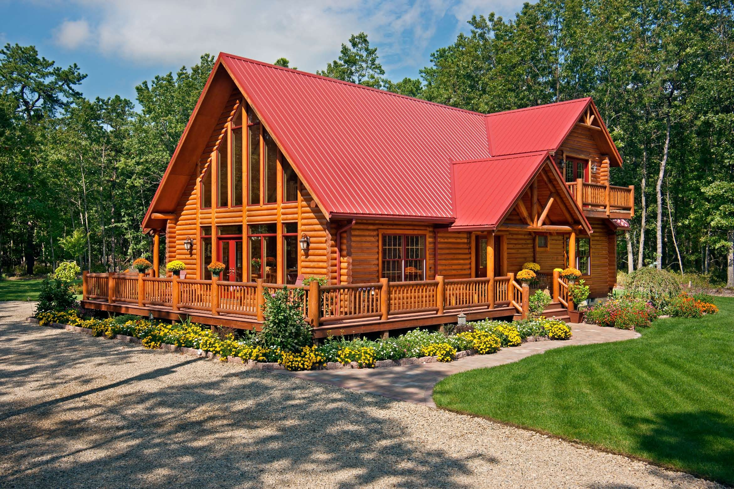 This Log Home Features A Red Metal Roof And A Wraparound
