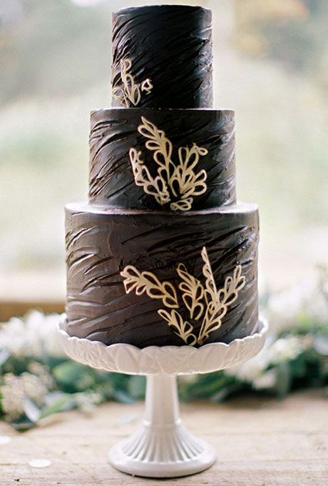 Brides.com: . A three-tiered chocolate wedding cake with white flower details, created by Sweet & Saucy Shop.