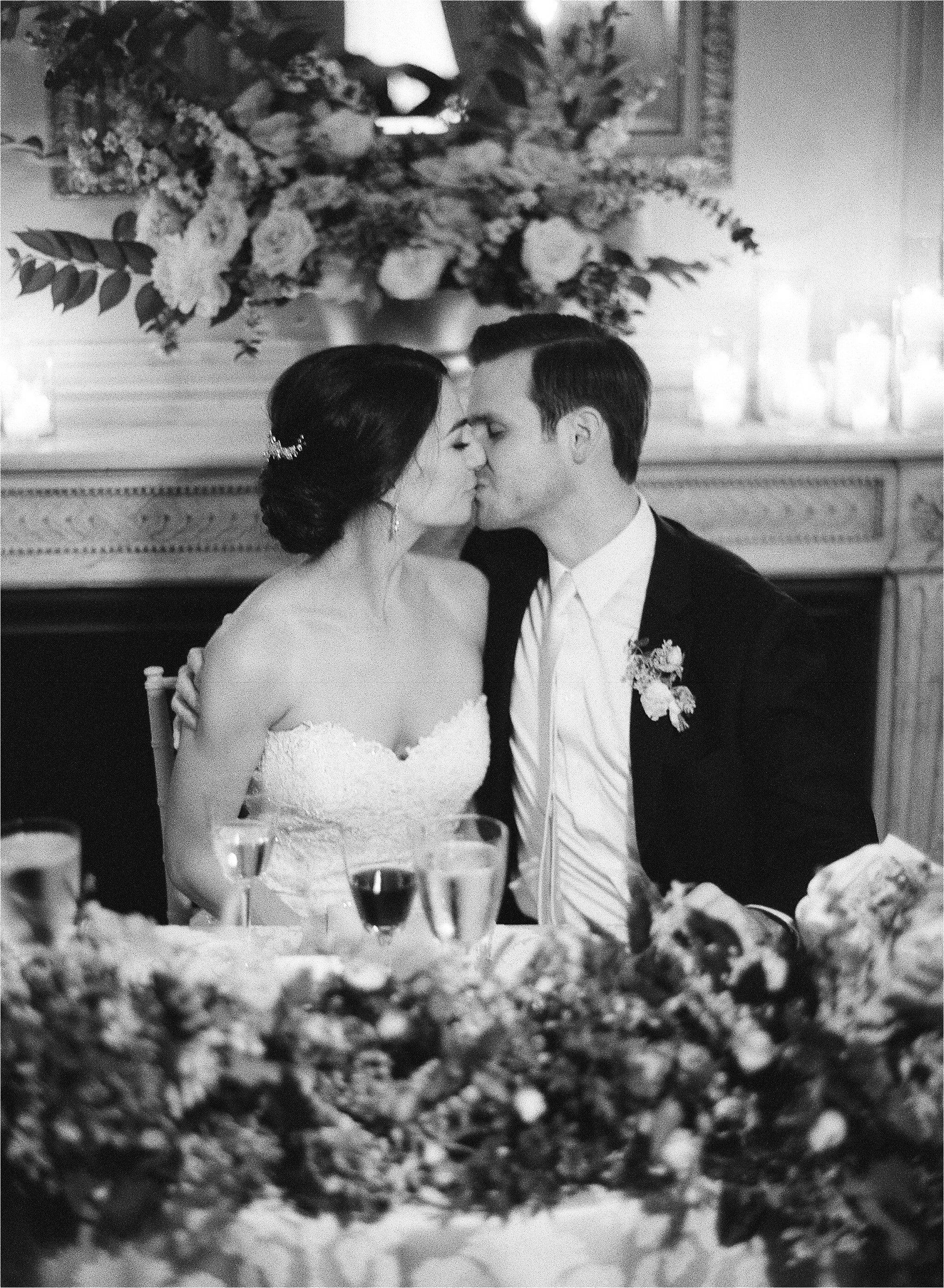 Timeless and romantic black and white photography of bride and groom kissing at the wedding table