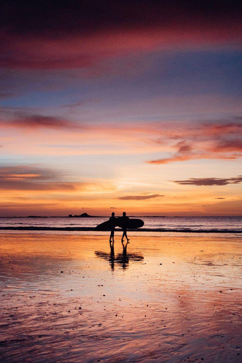 5ed5c65fa2 Surfer holding surfboard on the beach. Rainy Season Costa Rica Sunsets  sunset