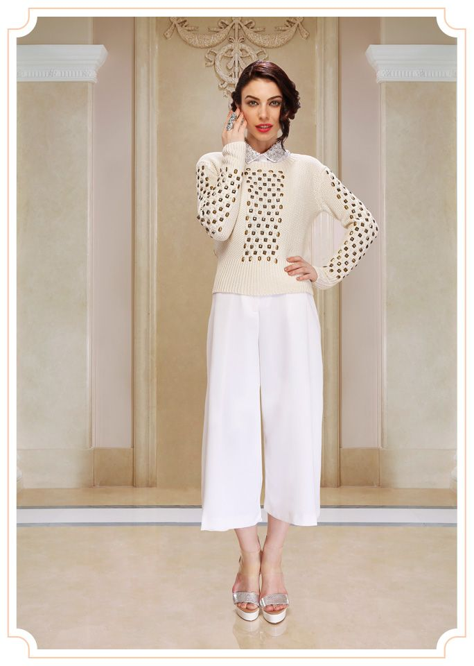 Soft ivory woollen sweater with antique metal work, paired with an ivory crepe three quarter pant